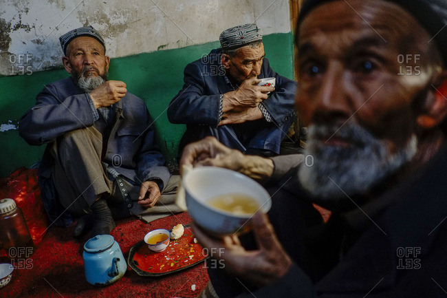 Kashgar, China - May 7, 2016: Uighur elders drinking tea at a secret tea house in old Kashgar