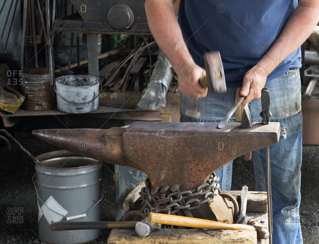 Blacksmith working at a forge at a county fair in Victoria, British Columbia, Canada