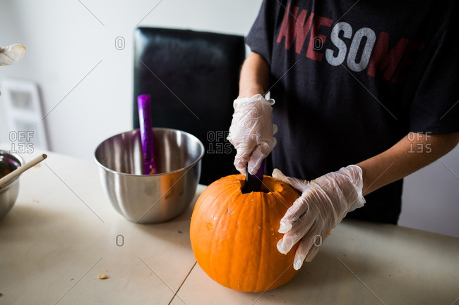 Boy carving a pumpkin and scooping the inside