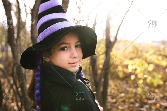 Little girl in a witch costume with purple braids