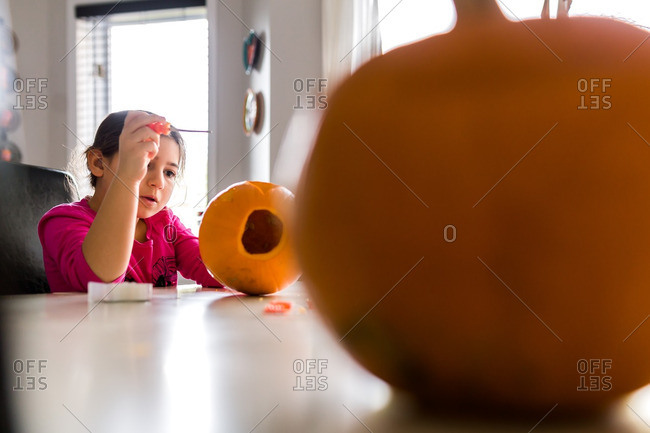 Girl carving a hollowed pumpkin for Halloween
