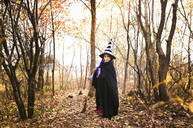 Girl in a witch costume holding a broom in the woods