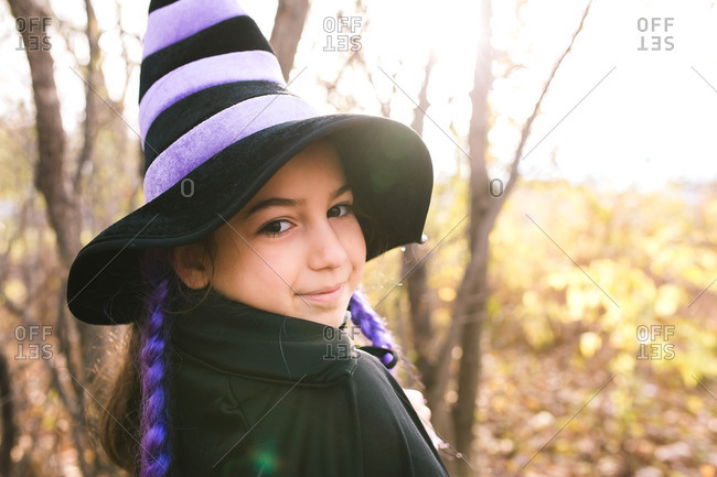 Little girl in a witch costume with purple braids standing in the woods