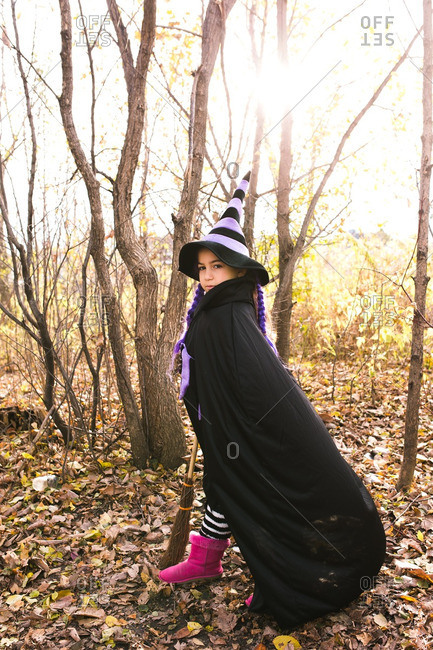 Girl wearing a witch costume standing in the woods