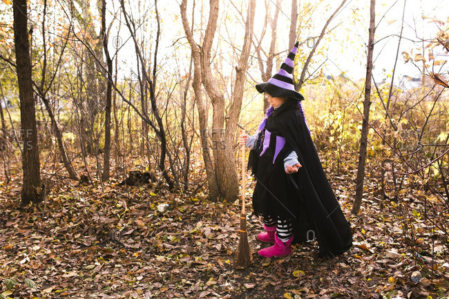 Girl in a witch costume holding a straw broom in the woods