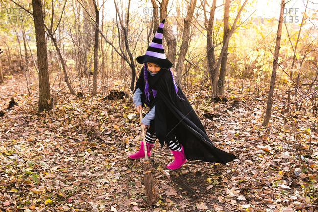 Girl in a witch costume sweeping leaves in a forest