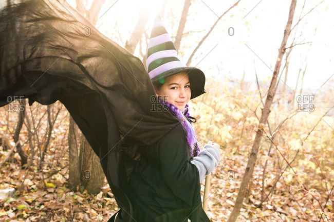 Girl in a witch costume with her cape fluttering behind her