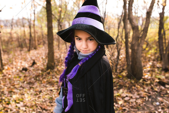 Girl in a witch costume in the forest making a serious face