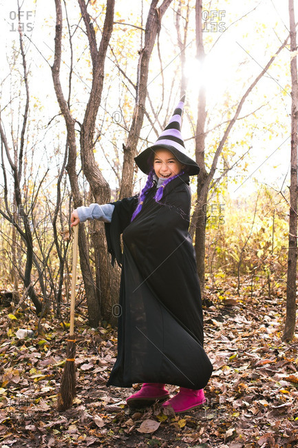 Girl in a witch costume smiling in the woods