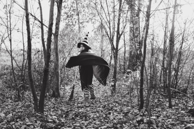 Little girl in a witch costume walking in the woods