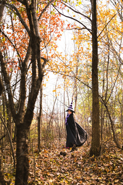 Girl in a witch costume standing beneath autumn trees