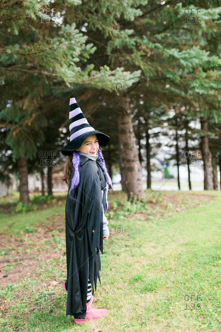 Little girl in a witch costume standing near trees
