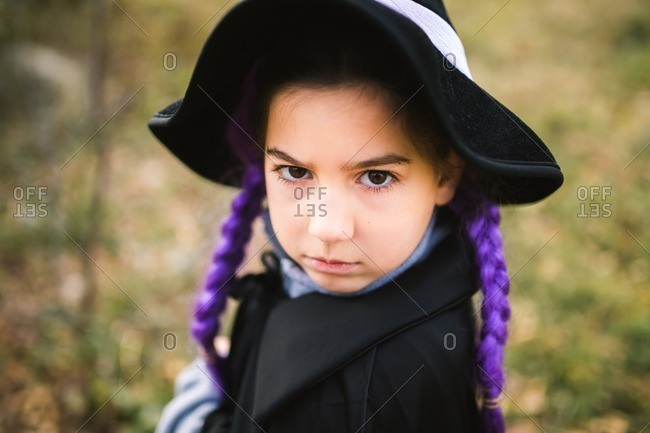 Little girl in a witch hat making a serious face