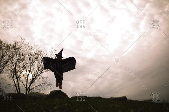 Little girl in a witch costume jumping on a rock