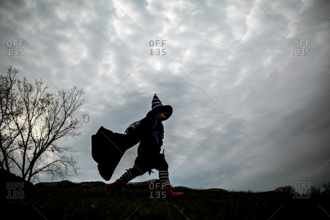 Girl in a witch costume walking across a grassy hill