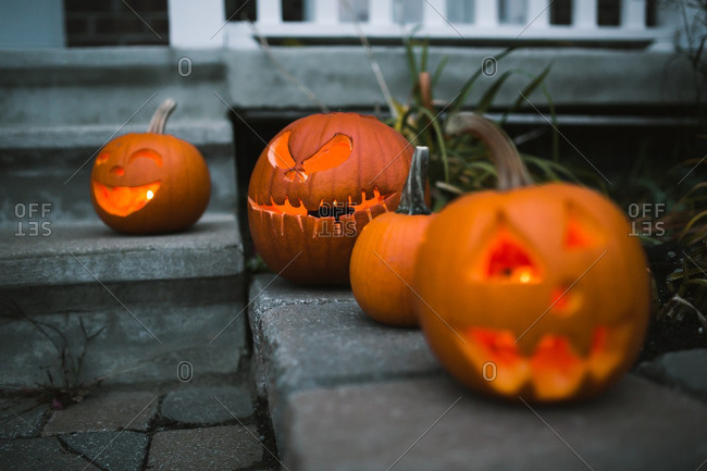 Illuminated jack-o'-lanterns on a stone walkway and stairs