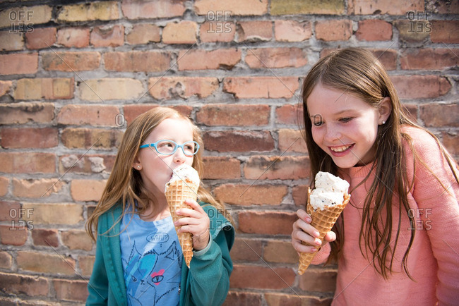 Two sisters eating ice cream cones in front of a brick wall