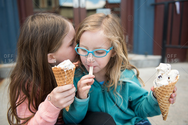 Two sisters whispering secrets and eating ice cream cones