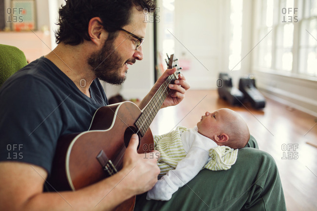 Man playing a song for his newborn baby in his lap