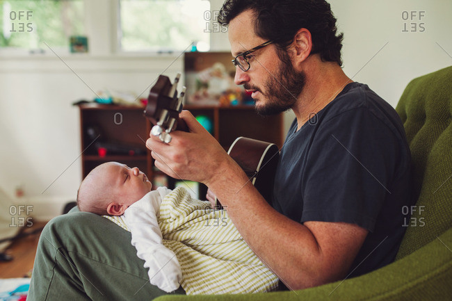 Father playing a song on his ukulele for his newborn baby
