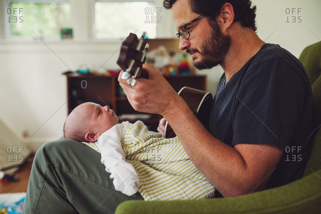 Father playing a song for his newborn baby in his lap