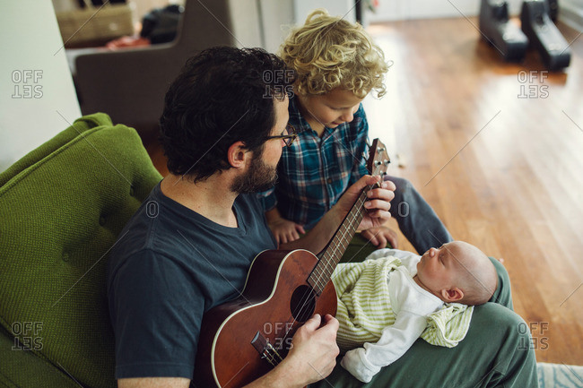 Man playing a song on his ukulele for his toddler son and newborn child