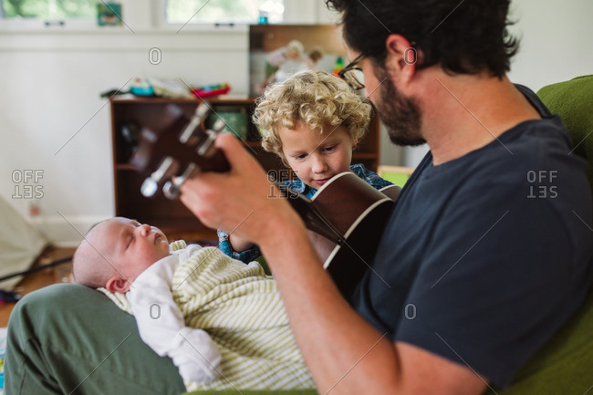 Father playing his ukulele for his newborn baby and toddler son