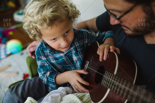 Boy sitting in his father's lap looking at a ukulele