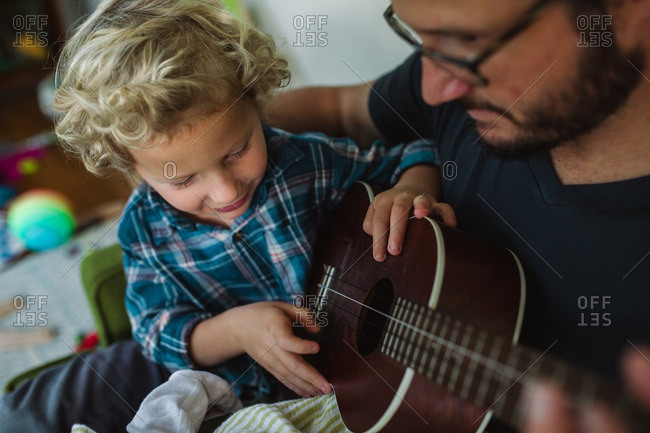 Boy looking at a ukulele while sitting in his father's lap