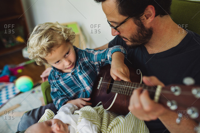 Man playing a ukulele for his newborn child and toddler son