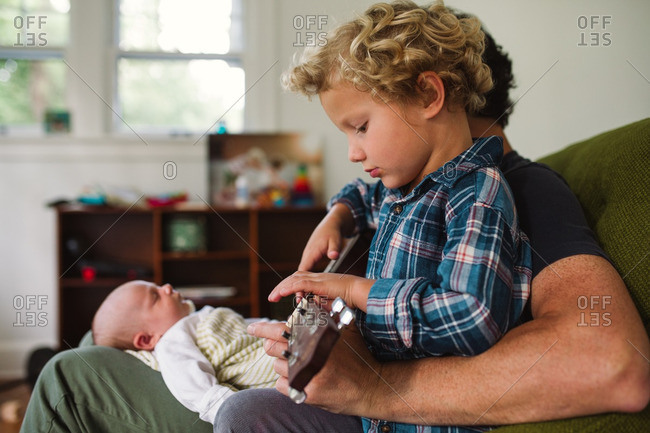 Man playing a song on a ukulele for his two children