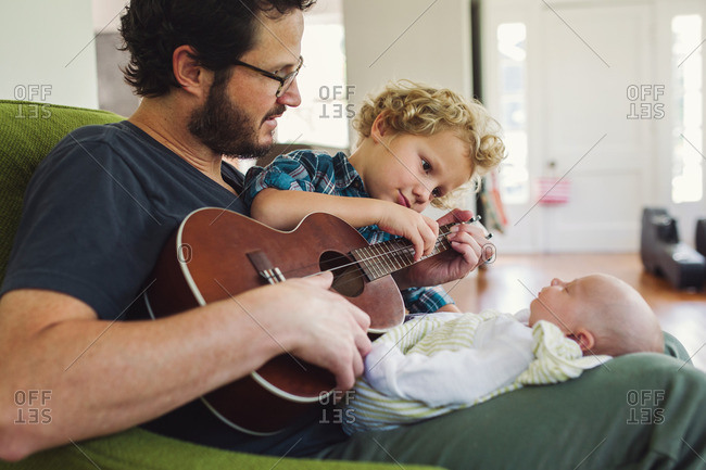 Man and toddler son playing a ukulele for a new baby