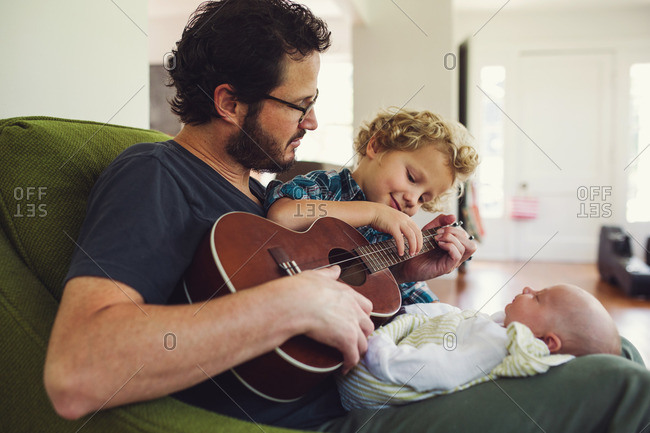 Father and toddler son playing a song on a ukulele for a newborn baby
