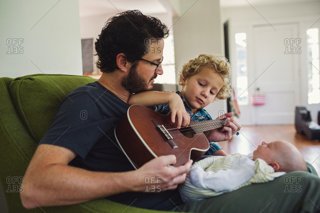 Father and son playing a ukulele for a newborn baby