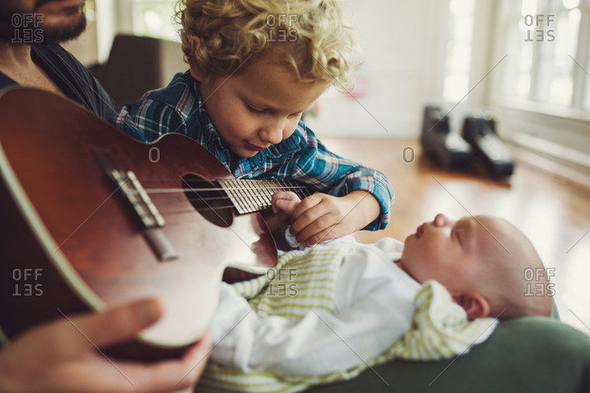 Little boy sitting in his father's lap with a ukulele and his newborn sibling