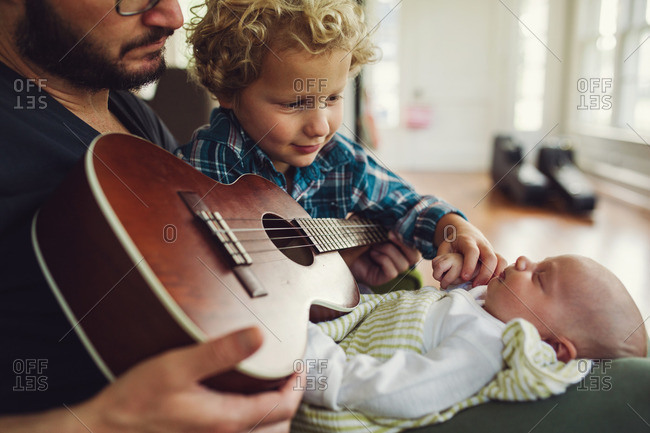 Man holding his toddler son and newborn in his lap with a ukulele