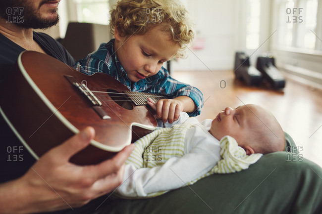 Toddler boy sitting in his father's lap with his new sibling and a ukulele