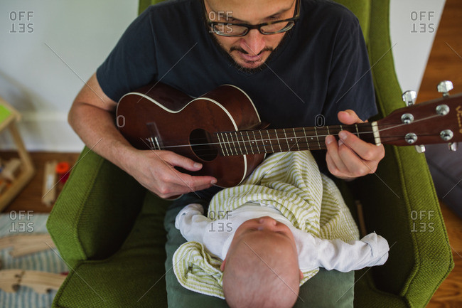 Father playing a song on a ukulele for his newborn child