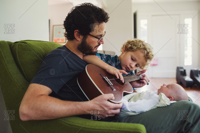 Father and son playing a ukulele for their new baby and sibling
