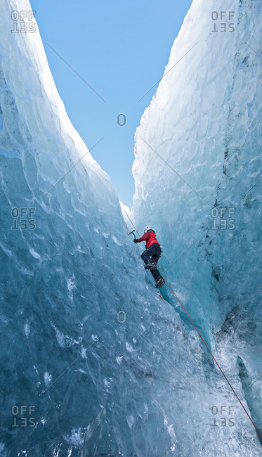 Climber climbing out of ice cave