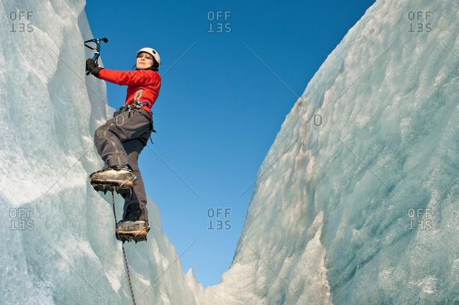 Climber scaling glacier wall