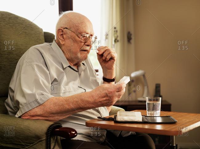 Older man taking medication in armchair