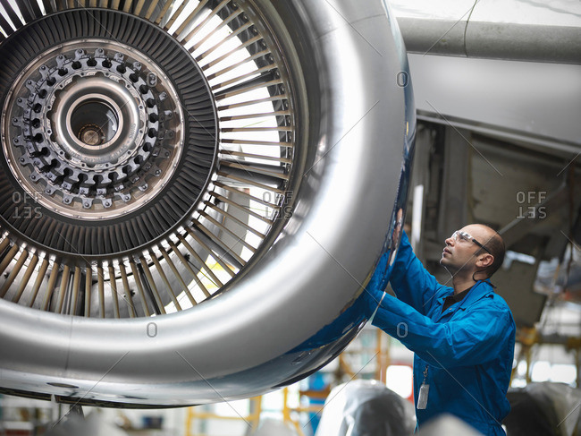 Aircraft engineer working on 737 jet engine in airport