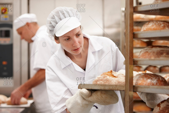 Chef carrying tray of bread in kitchen