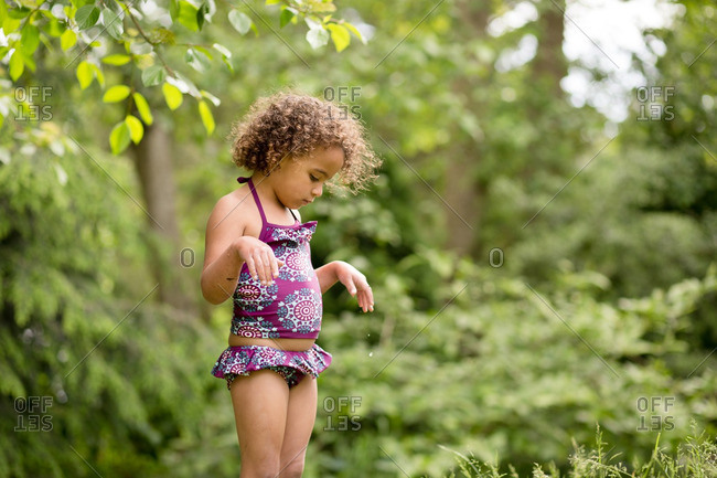 Little girl with curly hair and a purple swimsuit