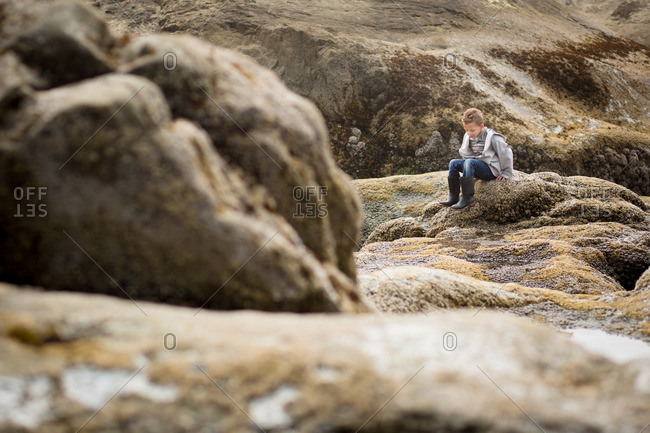 Boy sitting on mossy rock formations at a beach