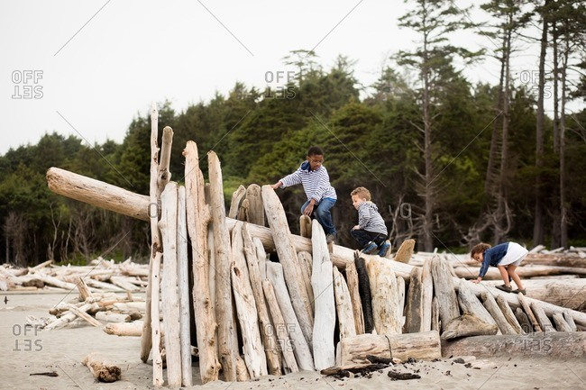 Three siblings climbing on a driftwood shelter on the beach