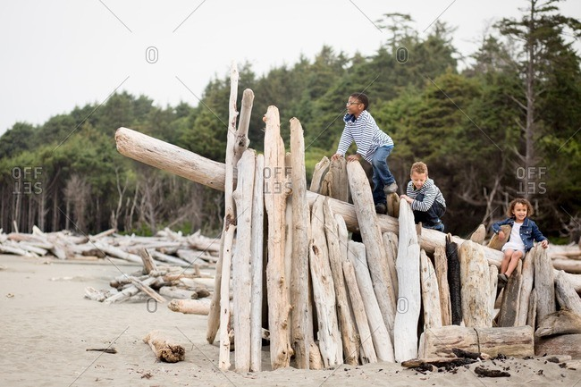 Brothers and sister exploring a driftwood shelter on a beach