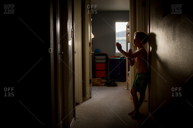 Boy practicing martial arts in a dark hallway