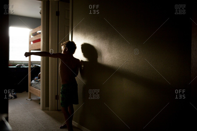 Boy standing in a dark hallway practicing martial arts moves